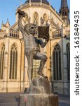 """Leuven - Tountain of wisdom or  """"Fonske"""" is a statue as symbol of students life by sculptor is Jef Claerhout and st. Peters cathedral in background"""