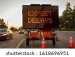 "Small photo of Mobile Electronic Traffic Sign stating ""expect Delays"" taken at sunset with traffic blurred driving past the sign and traffic cones"