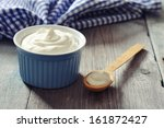 Greek yogurt in a ceramic bowl with spoons on wooden background