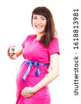 Small photo of Happy smiling pregnant woman in pink dress with blue ribbon showing number of ninth month of pregnancy, concept of extending family and expecting for newborn