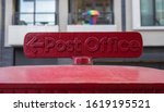 Red post office sign on top of...