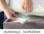 Woman Hiding Dollar Banknotes...