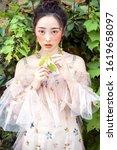 asian flowering girl in outdoor ... | Shutterstock . vector #1619658097