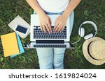 Young girl using laptop computer with headphones, smartphone and books on the grass in park