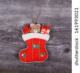 Christmas decorative ornament - Gifts in sock horses on wooden background - stock photo