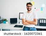 Portrait of confident graphic designer leaning on desk in office with arms crossed - stock photo