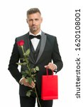 male elegance. valentine man black tux suit. man with present for love date. Black tie for formal events. tuxedo man with rose and shopping bag. happy valentines day. gift with love. shopping sale.