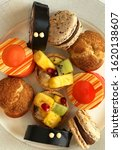 Small photo of Delicious traditional English high tea cakes on a plate, a mix of fruit tartlet with custard, roulade, eclaire, orange cheesecake and macaroon.