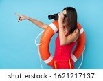 Small photo of Lifeguard woman over isolated blue background with lifeguard equipment and with binoculars while pointing far
