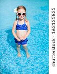 Portrait of adorable little girl at swimming pool - stock photo