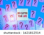 Small photo of Text sign showing De Clutter Your Life. Conceptual photo remove unnecessary items from untidy or overcrowded places Scribbled and crumbling papers with thick cardboard above wooden table.