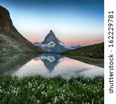 Matterhorn reflection in Riffelsee with flowers, Zermatt, Alps, Switzerland - stock photo