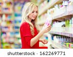 beautiful woman choosing personal care product in supermarket - stock photo