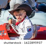 Goodwood, Sussex / UK - 15 September 2019: Smiling young driver, Briggs Griffin, sits behind the wheel of his red Austin J40 pedal car preparing to race in the Settrington Cup. He wears a cowboy hat. - stock photo