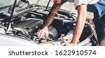 Professional car mechanic in uniform  fixing a car engine and repairing checking under the car hood in auto service  - stock photo