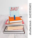 Small photo of Conceptual hand writing showing Bias. Business photo showcasing inclination or prejudice for or against one demonstrating group pile stacked books notebook pin color reminder white wooden.