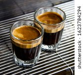Small photo of close up shot of a double shot of espresso in glass shot glasses, on the machine grate