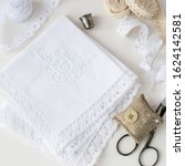 Small photo of Needlework. Two white handkerchiefs with lace trim, pillow for needles, scissors, lace and a thimble on a light background. Selective focus.
