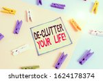 Small photo of Conceptual hand writing showing De Clutter Your Life. Business photo showcasing remove unnecessary items from untidy or overcrowded places Colored clothespin paper reminder with yellowblue background.