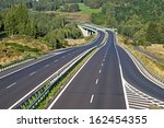 empty highway between forests...   Shutterstock . vector #162454355