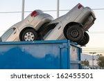 2 Junk Cars In A Dumpster