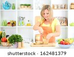 happy smiling woman in kitchen... | Shutterstock . vector #162481379