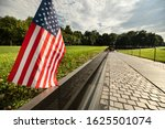 Small photo of Washington DC, USA - June 26, 2018: People pay tribute to the lost soldier names inscribed on the Vietnam Veterans War Memorial on the National Mall