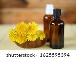 Small photo of Dandelion tincture. Herbal tincture. Medicinal herbs. Medicinal tincture in glass bottles and dandelion flowers on a wooden background.infusion of healing herbs. Homeopathy