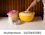 Small photo of Hand knead dough in the yellow bowl on wooden table. Creativity, adult.