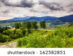 valley near forest on a steep mountain slope before the rain in morning mood - stock photo