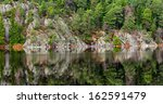 Shore at forest on granite rock during autumn, mirrored - stock photo