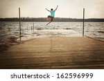 Teen Boy Jumping Off A Dock