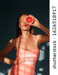 Small photo of Young woman with freckles and wet hair summer style standing isolated on blue background holding grapefruit half covering eye posing to camera pouting lips grimace silly