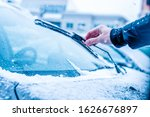 Windshield wiper in hand. Concept of cleaning and maintaining the wiper during winter - stock photo