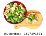 Aubergines kermit eggplants pieces in a  red bowl and wooden cutting board, isolated on white background.