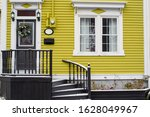 A Yellow House With White...