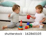 Two Barefoot Kids Sit On Carpe...
