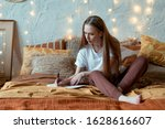 Small photo of Calm and inspirited young adult girl making notes in organizer, resting in bedroom, spending morning at home, sitting on bed