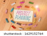 Small photo of Text sign showing Project Planning. Conceptual photo plan and subsequently report progress within the project Colored clothespin papers empty reminder wooden floor background office.