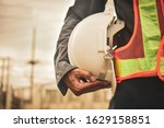 Close up hand holding white helmet hard hat Engineering concept - stock photo