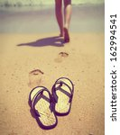 slippers on sand, and female feet out of focus ,with a retro effect