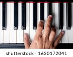 Small photo of right hand playing a E Major chord on the piano