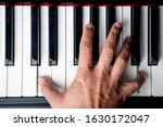 Small photo of right hand playing a D octave chord on the piano