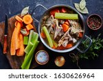 Small photo of hot chicken stock with vegetables and aromatic herbs in a stockpot, ingredients on a kitchen worktop, close-up, flat lay