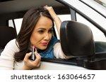 woman applying lipstick on her... | Shutterstock . vector #163064657