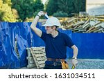 Small photo of Young workman with helmet enjoy dancing while listening to music at construction site background