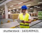 Small photo of Portrait of caucasian warehouse worker with tablet standing in storage department. Male worker checking goods dispatch in factory.