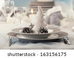 Christmas table setting. Restaurant place setting in elegant holiday style with xmas ornaments - stock photo