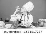 Small photo of Finger licking good. Pretty woman chef gesturing ok. Kitchen maid preparing vitamin food. Professional cook with vitamin vegetables on table. Vitamin nutrition. Getting vitamin the natural way.