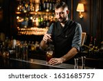 Small photo of Male bartender in stylish clothes stirring alcohol cocktail with special bar spoon